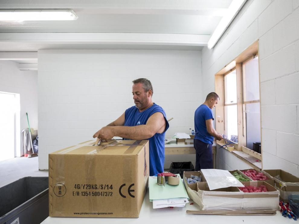 Ángel y Marius preparan carcasas en una caseta de montaje con ventanas protegidas.