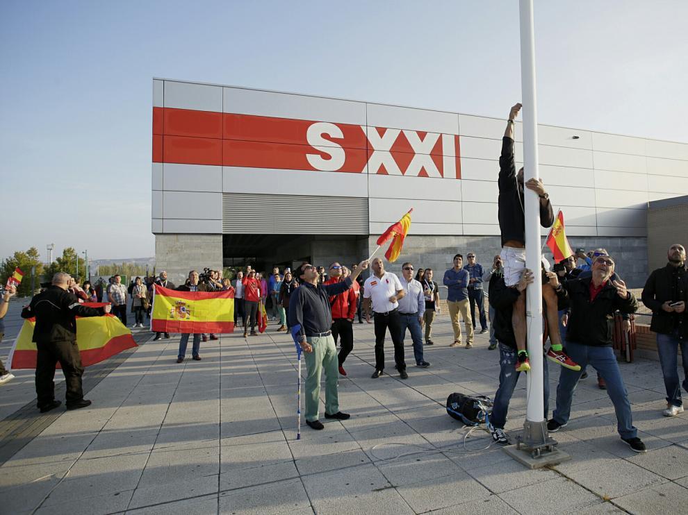 Varias personas han izado la bandera española a las puertas del pabellón siglo XXI.