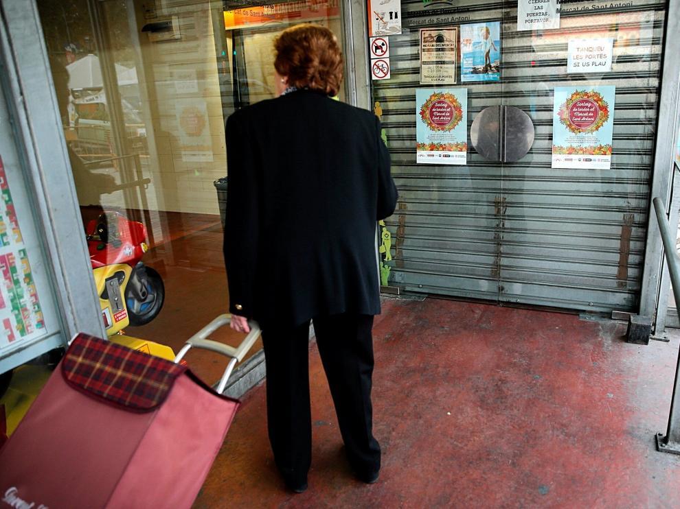 Una mujer ante las puertas cerradas en el mercado de San Antoni