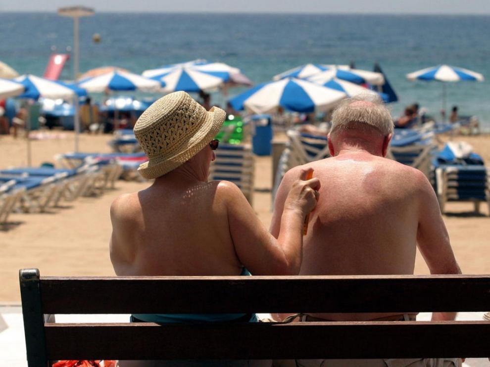 Dos turistas toman el sol en la playa de Benidorm, una de las más típicas dentro del programa del Imserso.
