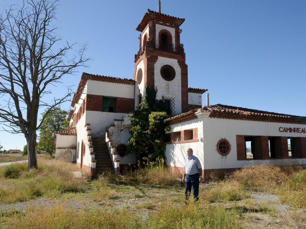 El alcalde de Caminreal, Joaquín Romero, delante del edificio de la estación, que tiene una torre.