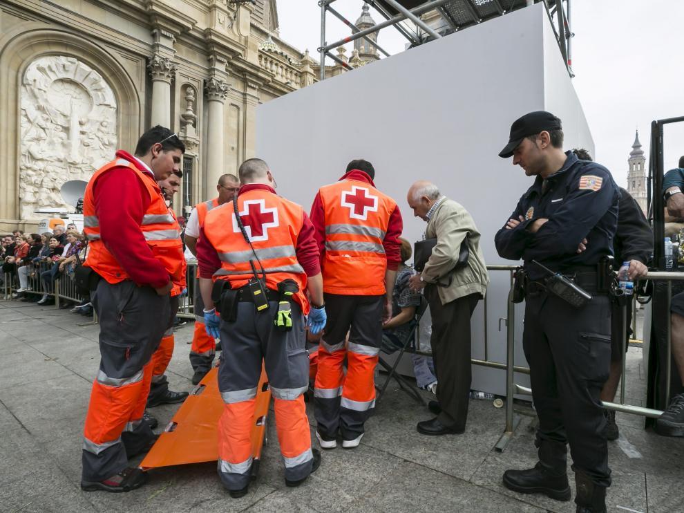 Varios voluntarios de Cruz Roja atienden a una persona durante la Ofrenda de Flores.