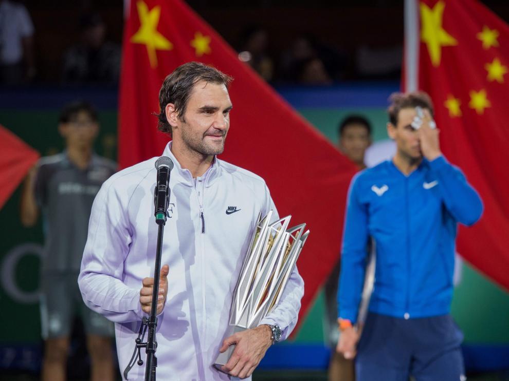 Federer, en primer plano, se dirige al público tras derrotar a Nadal, al fondo de la imagen.