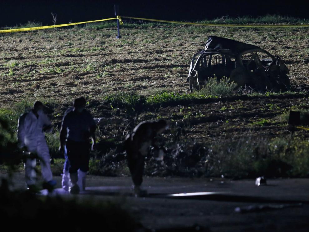 Los forenses revisan el lugar donde explotó el vehículo de la periodista.