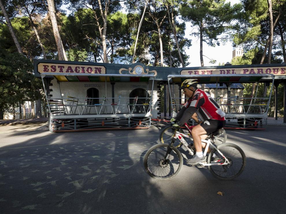 Un ciclista circula frente a la carrocería del tren chuchú del parque.