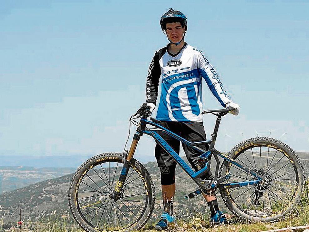 El joven Gabi Torralba posa con su bicicleta y su equipación habitual.