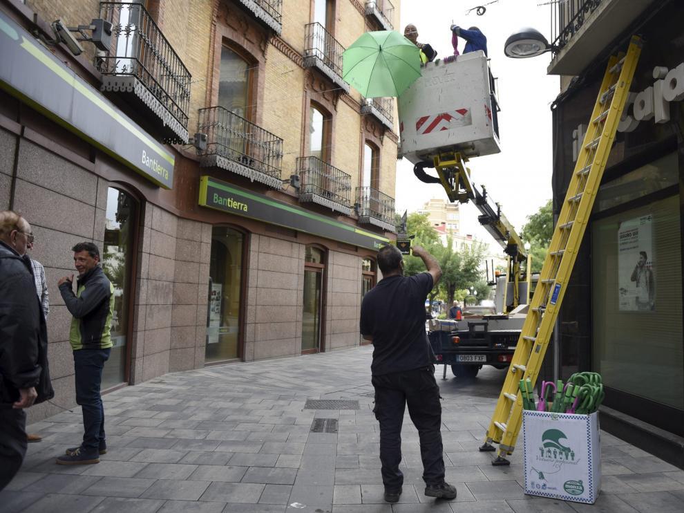 Trabajadores de las brigadas colocan los paraguas junto a la Asociación contra el Cáncer. verónica Lacasa