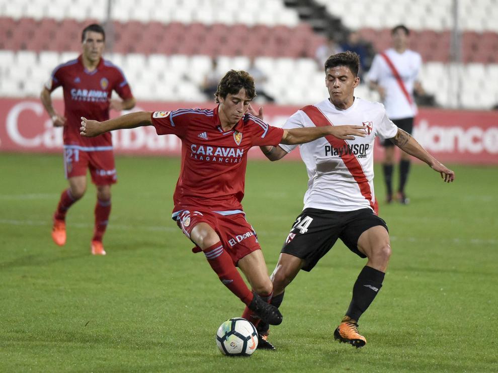 Julián Delmás avanza con la pelota ante la oposición de Felipe Carballo.