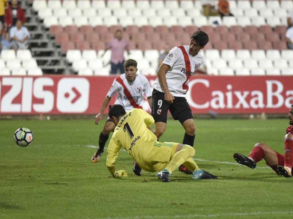 Verdasca y Cristian Álvarez por los suelos en el momento en el que Carlos Fernández, de rebote y de tacón, se aprovecha para anotar el 1-0 a favor del Sevilla Atlético.