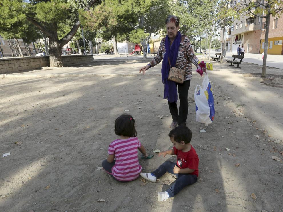 Una señora atiende a sus nietos en una de las zonas del parque de San Martín de Huesca.