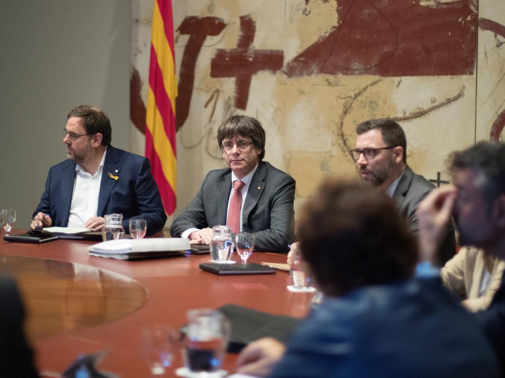 El presidente de la Generalitat, Carles Puigdemont (d) y el vicepresidente, Oriol Junqueras (i), durante la reunión semanal del gobierno catalán, a dos días de que el Parlament se reúna para acordar una respuesta a la aplicación del artículo 155 de la Constitución, asunto que analizarán en comisión los ocho senadores designados por la cámara catalana.