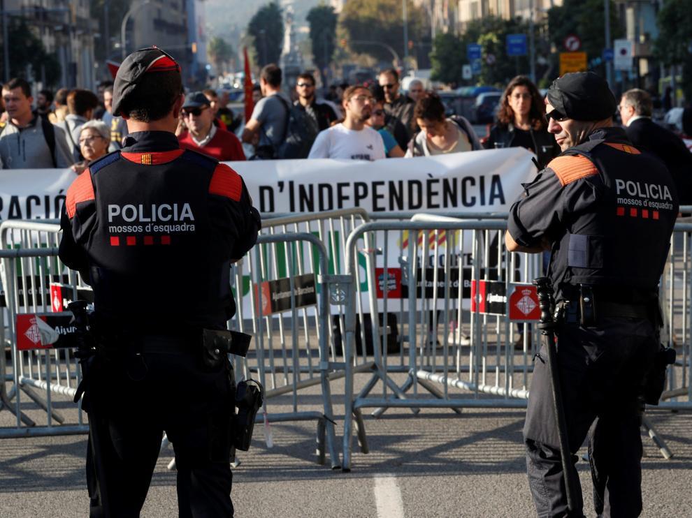 Dos mossos vigilan la concentración de personas que van llegando ante el Parlament este viernes.