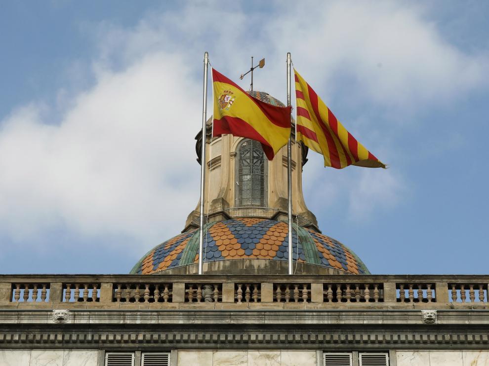 Las banderas española y catalana ondean en la fachada del edificio de la Generalitat en la plaza San Jaume de Barcelona.