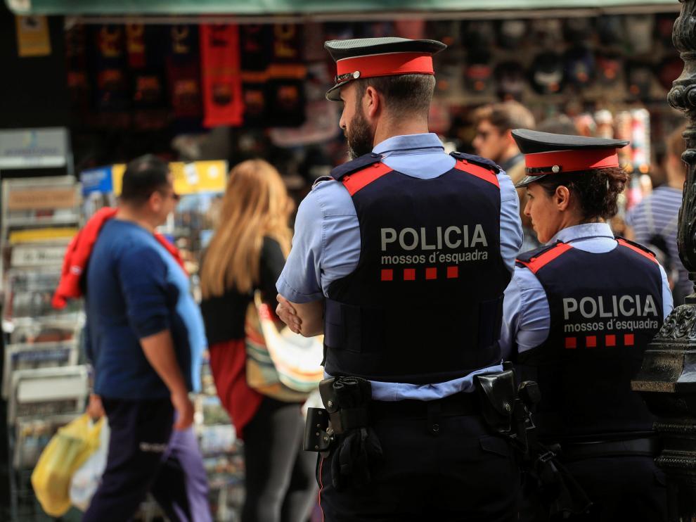 Dos mossos velan por la seguridad en una calle de Barcelona, este sábado.