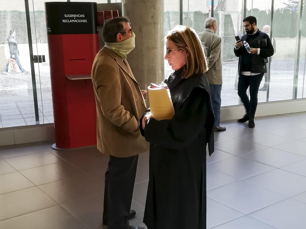 El acusado se cubre la cara con una braga en los pasillos de la Audiencia, antes de comenzar el juicio.