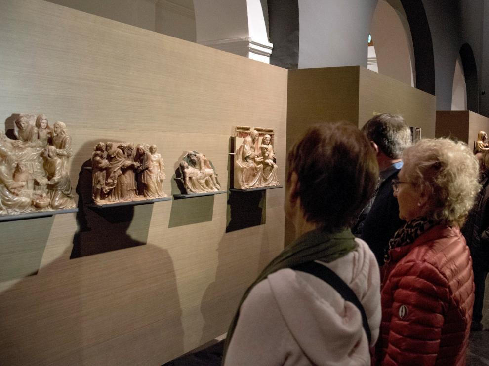 Varios visitantes admirando las obras de Sijena expuestas en el Museo de Lérida.