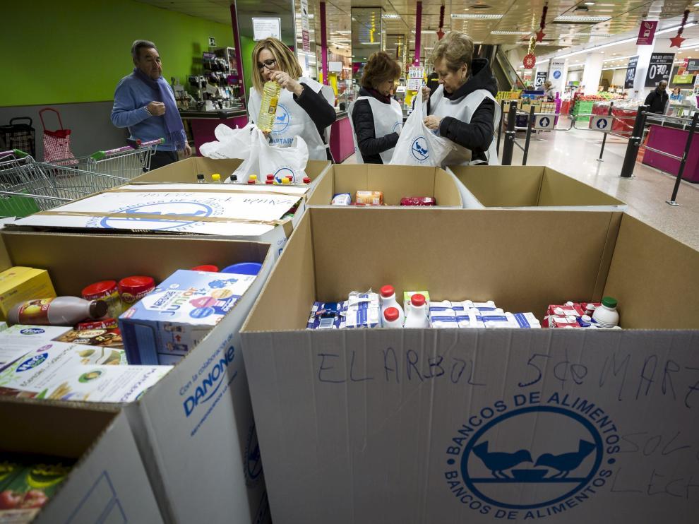 Aurelio Forcano, Isabel Gargallo, Araceli Giral y Merche García, todos ellos voluntarios, clasifican los alimentos.