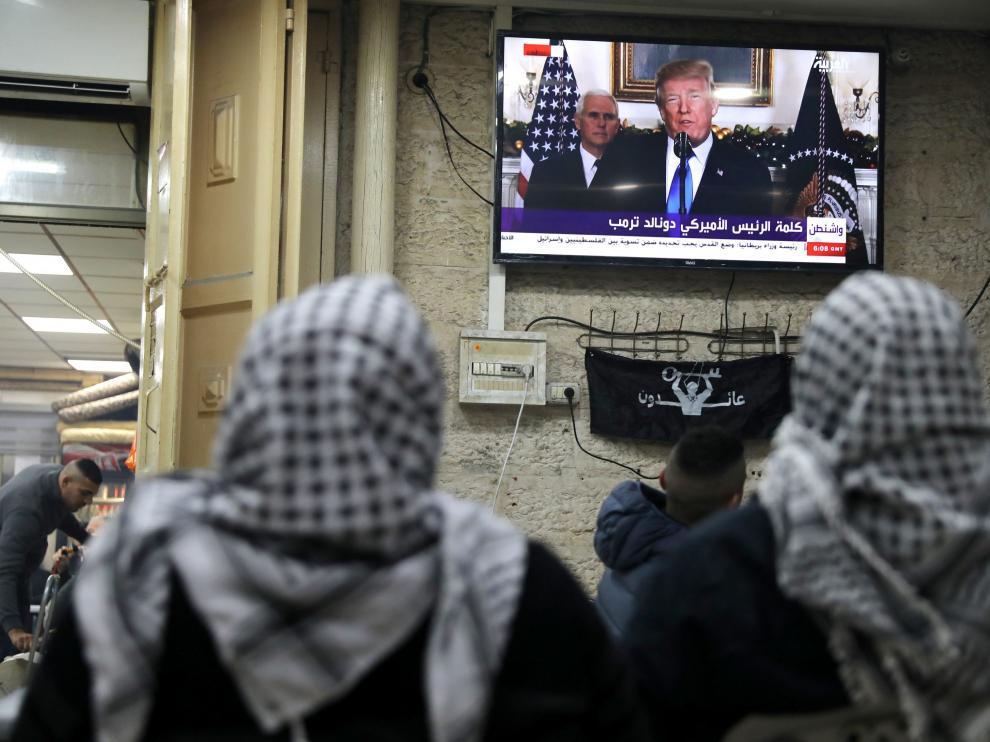 Dos palestinas ven por la televisión el anuncio de Trump.