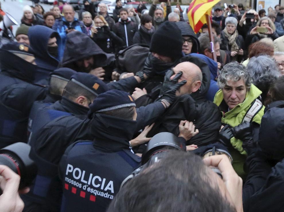 Varios agentes de los Mossos d'Escuadra empujan a los manifestantes a primera hora de la mañana de ayer.