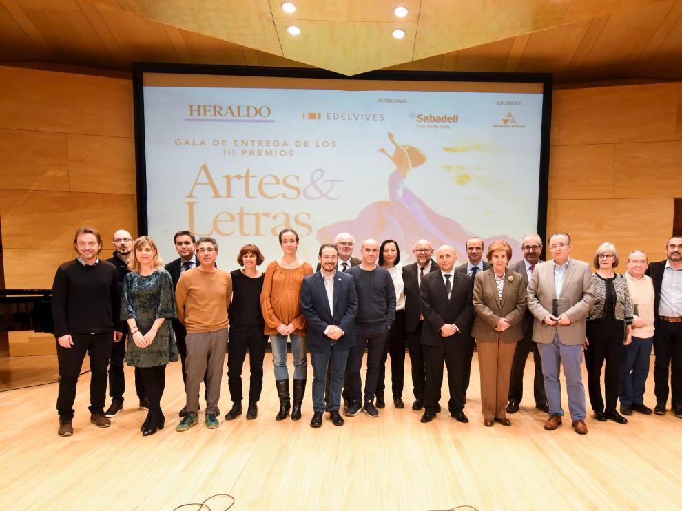 Los premiados por el suplemento 'Artes & Letras' y los encargados de entregar las distinciones, sobre el escenario de la sala Luis Galve al término de la gala.