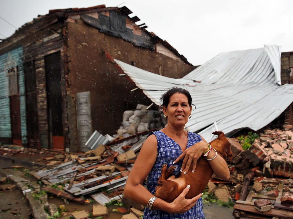 Una mujer posa junto a su casa destruida por el huracán Irma en Cuba