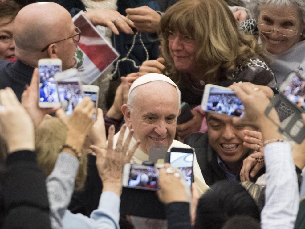 El papa Francisco saluda a las personas que asistieron a su audiencia semanal en el Vaticano.