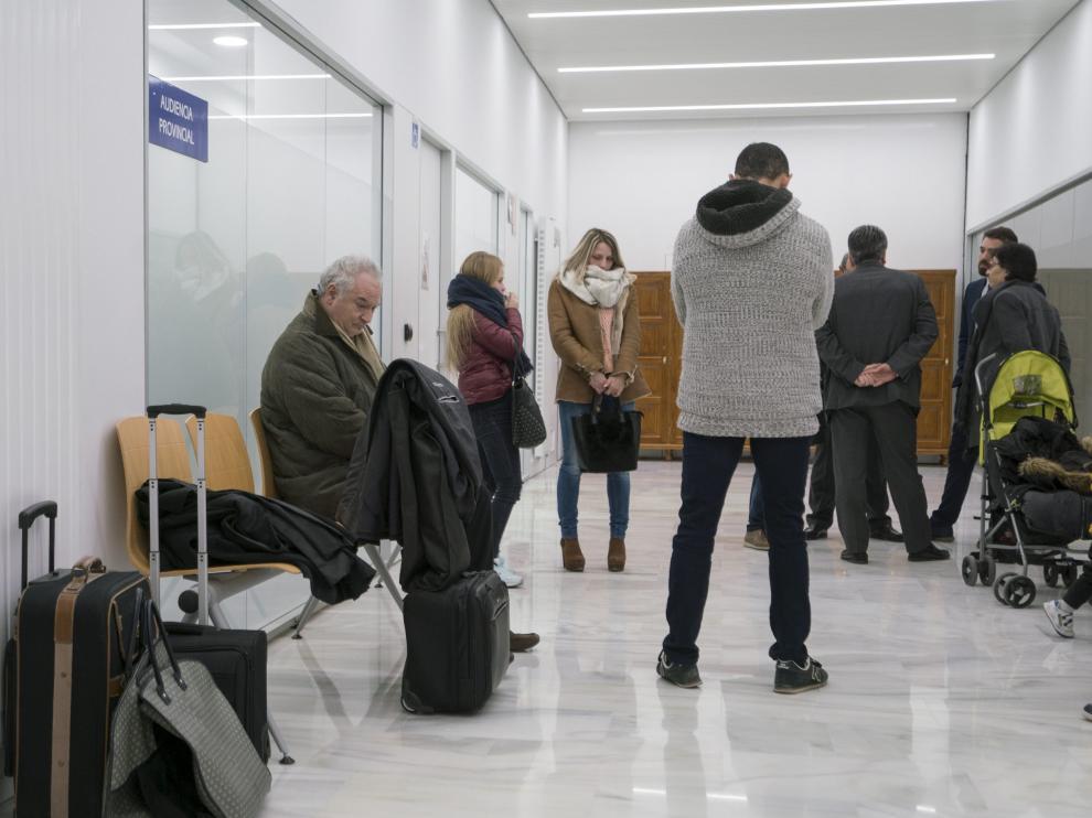 El pasillo de la Audiencia Provincial de Teruel, donde este lunes acusados y acompañantes aguardaban el inicio del juicio. En primer término, sentado, el principal acusado.