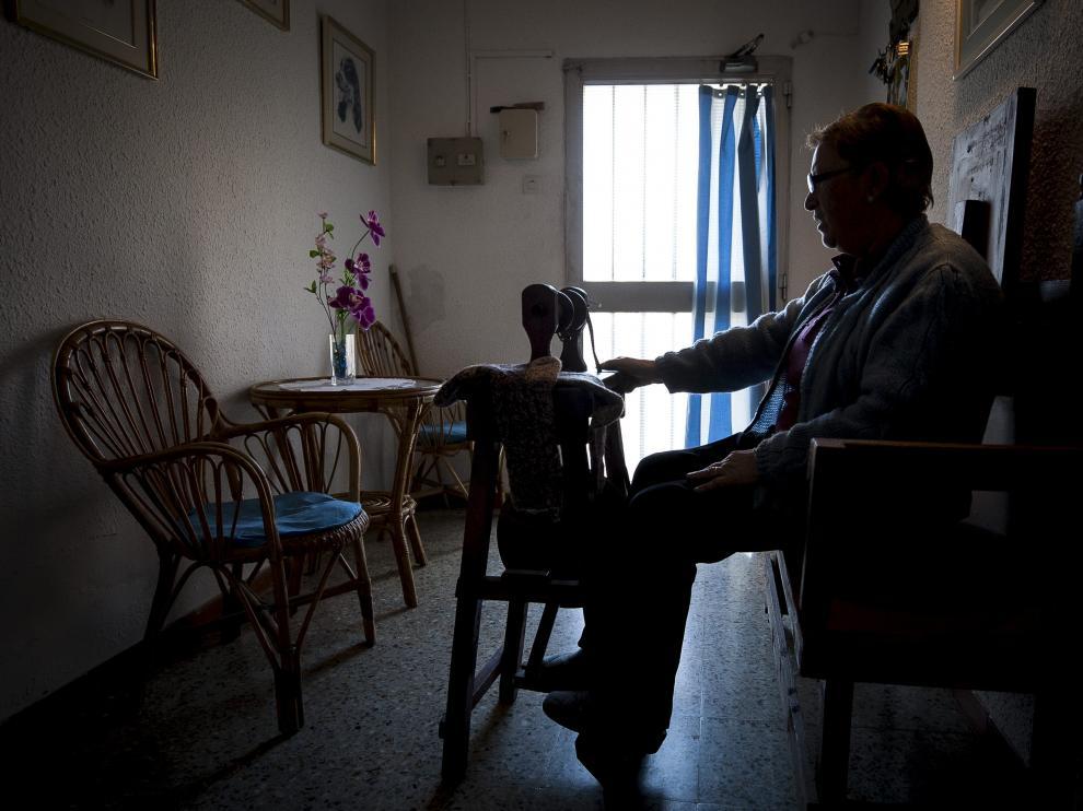 Emilia Puértolas se aplica con la máquina de hilar en el recibidor de su vivienda.