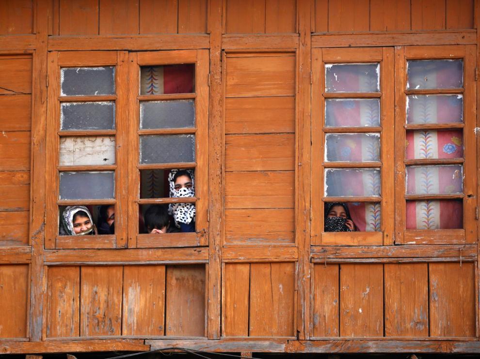 Varias mujeres miran por una ventana en la Cachemira india