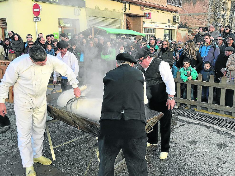 Los asistentes observan cómo se prepara el cerdo una vez que se ha realizado la matanza.