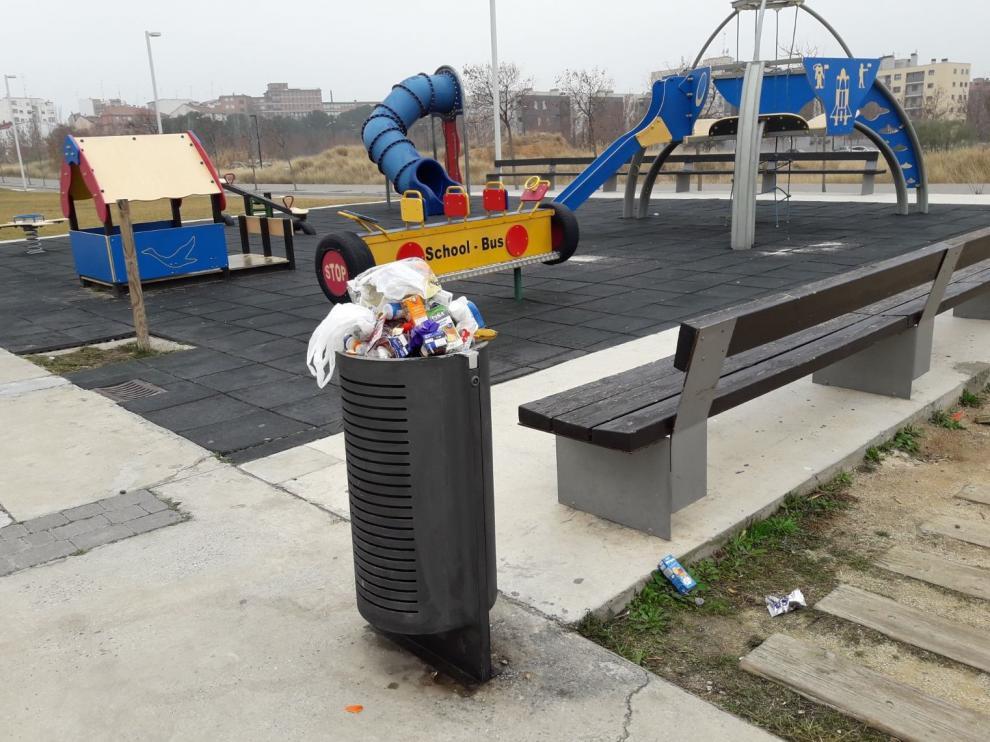 Las papeleras rebosan en el entorno del CEIP Julio Verne por la falta de limpieza