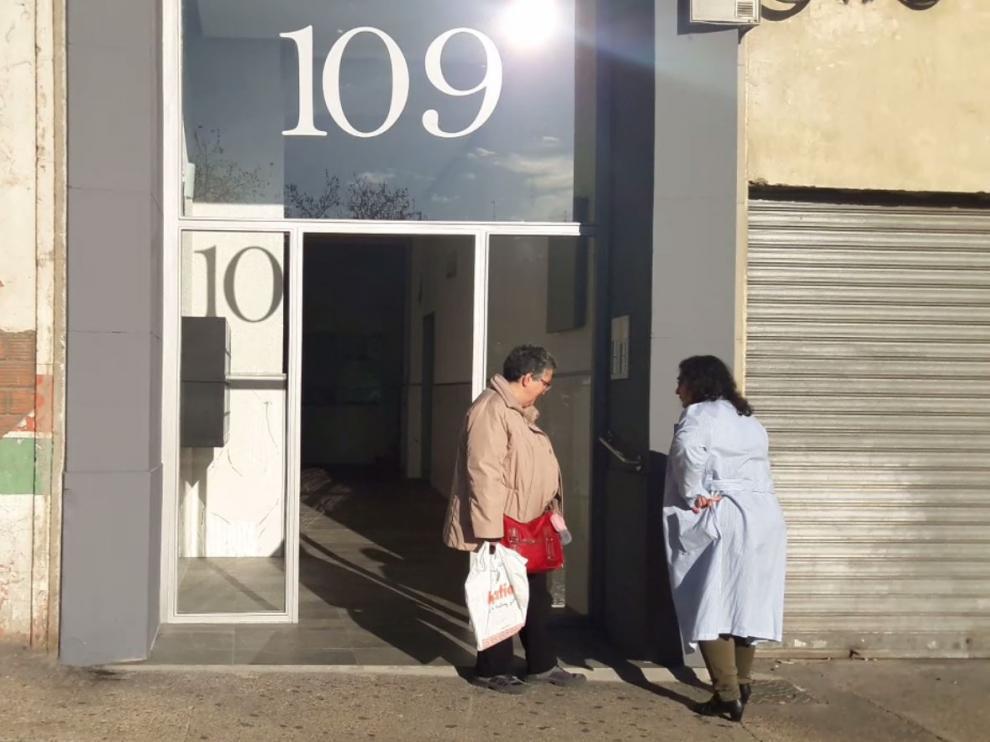 Dos vecinas observan la puerta robada en el número 109 de la calle Miguel Servet, en Zaragoza.