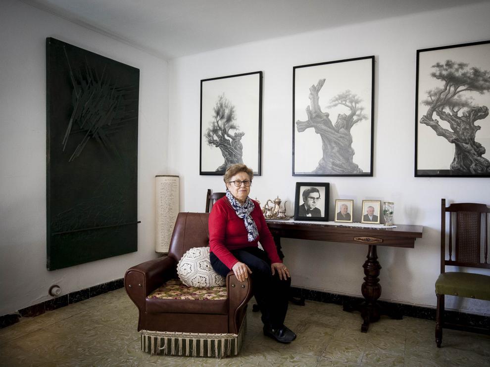 Manuela Fuertes, la hermana del desaparecido dibujante y pintor singrano; tras ella, tres obras del artista.