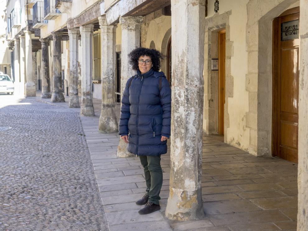 La responsable de la Oficina de Turismo, Milagros Gil, entre los soportales de la plaza Mayor de Mosqueruela.