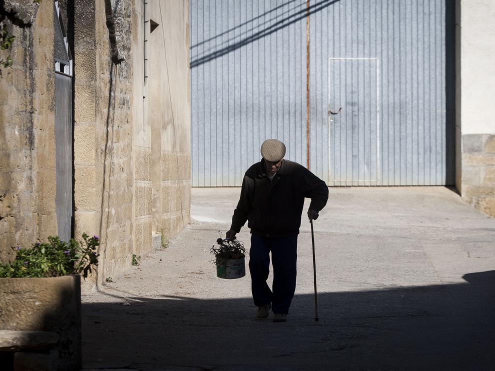 Un vecino de Biscarrués pasea al mediodía por el centro del pueblo.