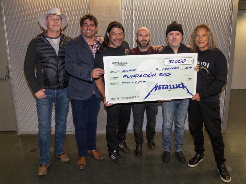 Los integrantes de Metallica posando con el cheque de la donación en Madrid.