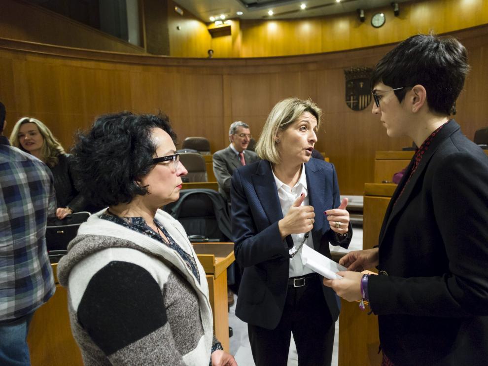 La coordinadora de la ponencia de la ley de renta básica, Pilimar Zamora, entre las diputadas de Podemos Amparo Bella y Violeta Barba, en el pleno.