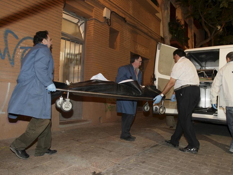 Momento en el que la Hermandad de la Sangre de Cristo sacaba el cadáver de la víctima de su domicilio, en el número 3-5 de la calle Cortesías de La Magdalena.