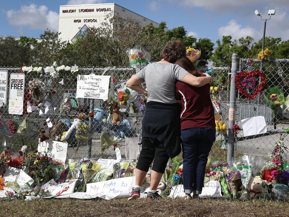 Dos personas mirando el memorial en homenaje a los 17 asesinados en el tiroteo.