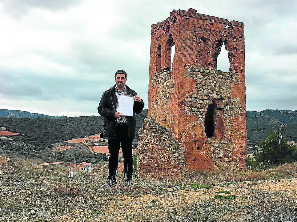 El alcalde de Cosuenda, Óscar Lorente, muestra las escrituras del terreno, junto a la torre.