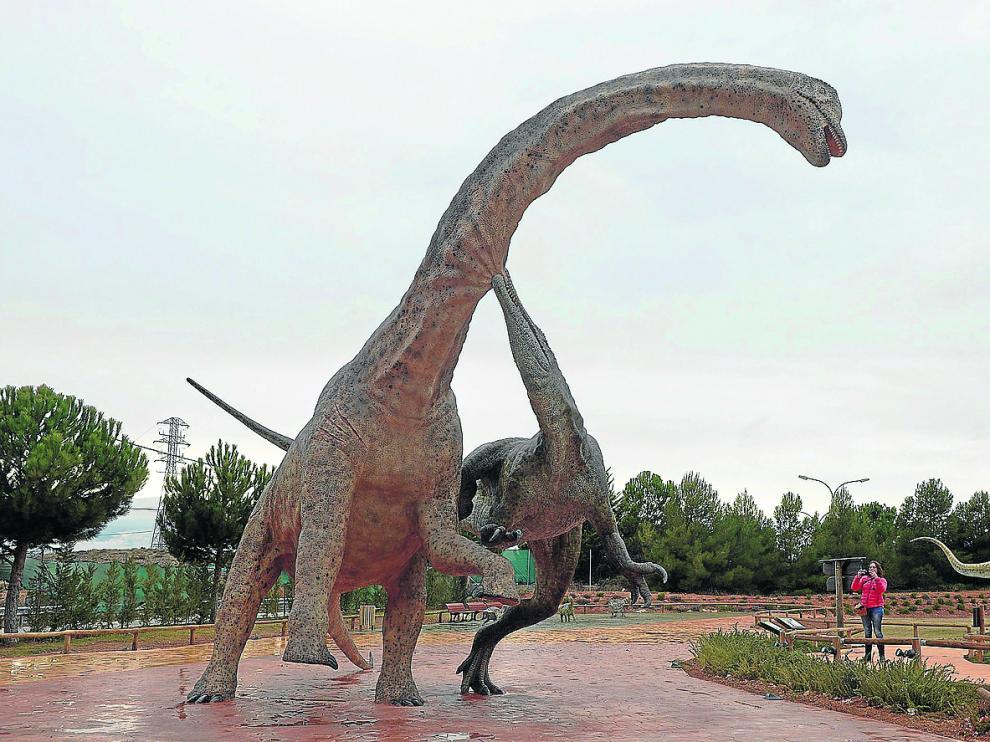 Un visitante de Dinópolis fotografía la reproducción de un Tastavinsaurus y un Baryonyx luchando entre sí.