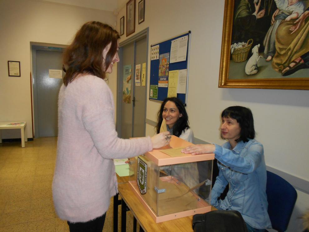 Una madre del colegio Sagrada Familia deposita su voto en la urna