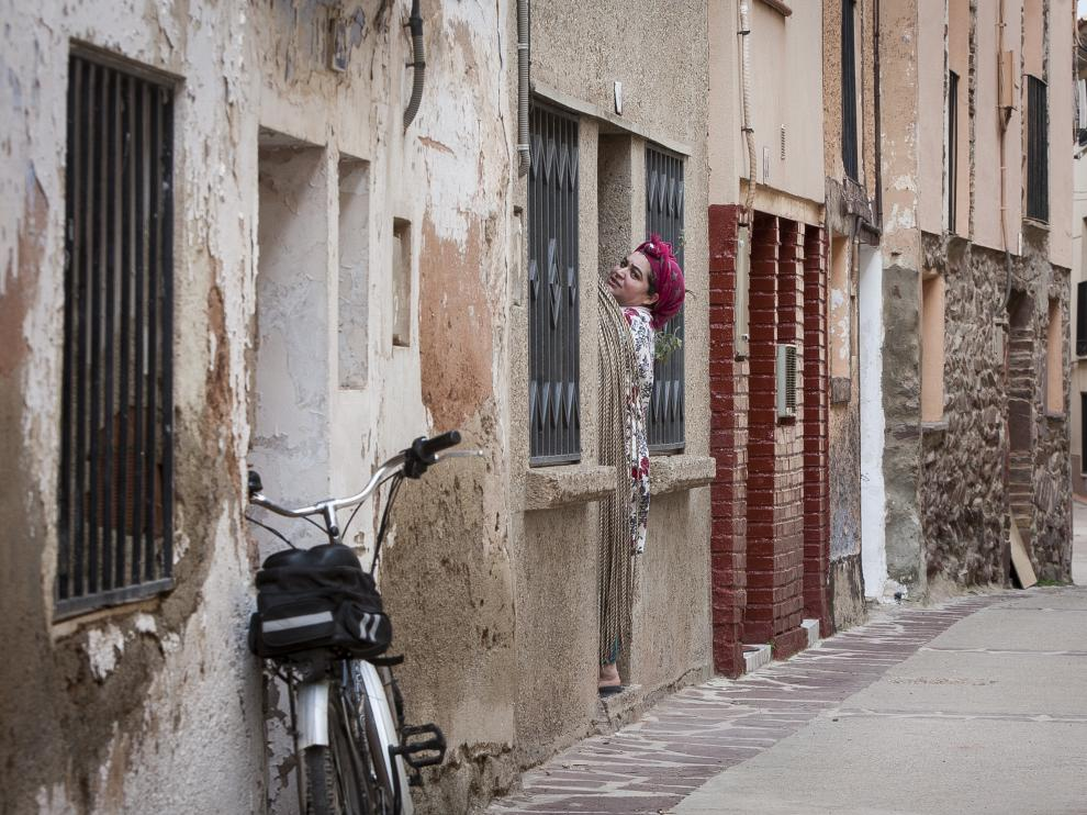 Una vecina se asoma a la calle desde el portal, en el centro de Tabuenca.