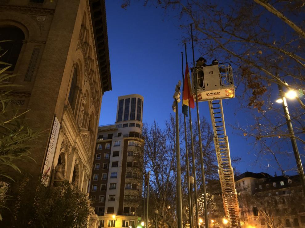 Los bomberos bajan a mitad de asta las banderas frente al Paraninfo.