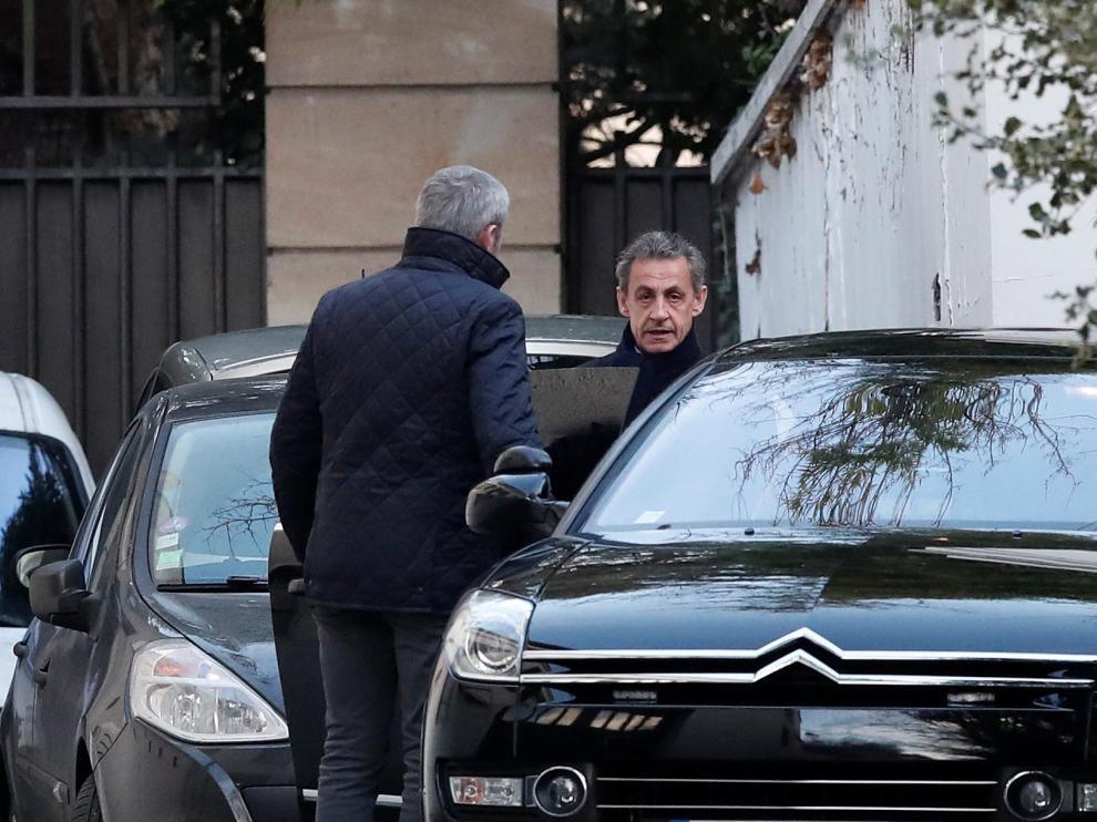 Sarkozy  saliendo de su domicilio en París acompañado por su abogado para dirigirse al interrogatorio