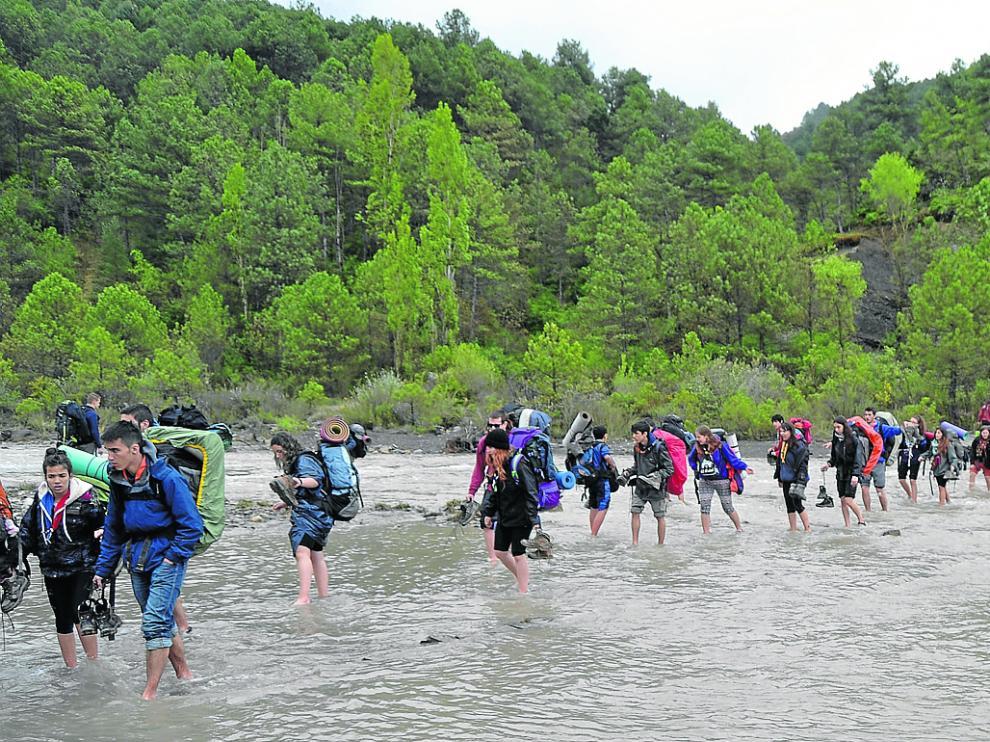 Los participantes en los campamentos tienen que cruzar el río para llegar al pueblo de Griébal.