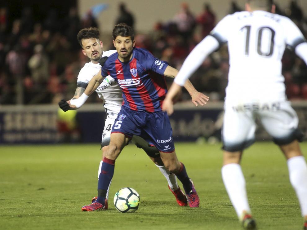 Juan Aguilera presionado por Rubén García durante el Huesca-Sporting del lunes (0-2).