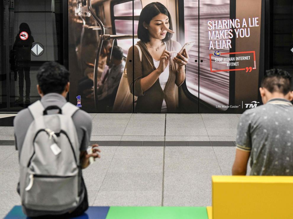 Ciudadanos esperan al tren enfrente de una nuncio que advierte sobre las noticias falsas