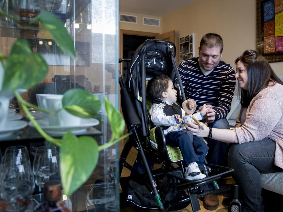 Las familias piden agilizar los pagos. Javi, de dos años y medio, con sus padres Alberto e Inés.