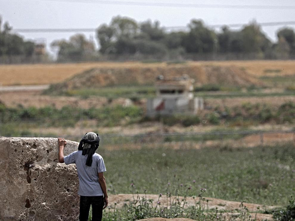 Un niño palestino observa una torre militar israelí días antes de la protesta 'La Marcha del Retorno' en la frontera de Gaza
